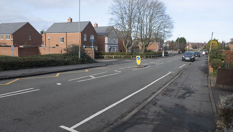 Road showing a long H-bar marked on the road with a car approaching