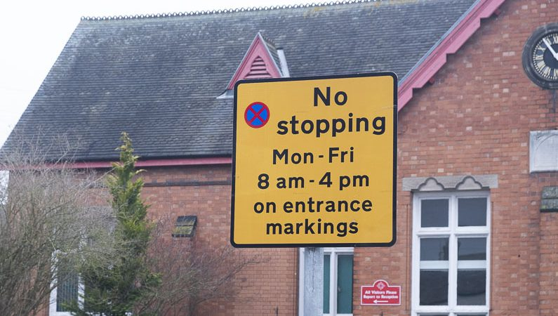Yellow sign showing No stopping Monday to Friday from 8am to 4pm on entrance markings