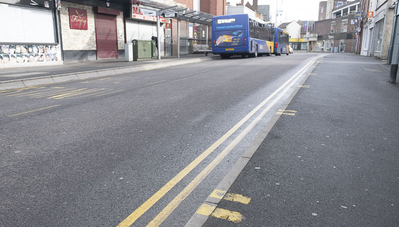 No waiting and loading yellow lines on the road and pavement with 2 buses in the background on the other side of the road
