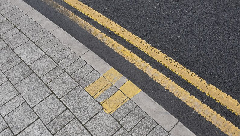 Yellow lines on the road and pavement to show no waiting and loading