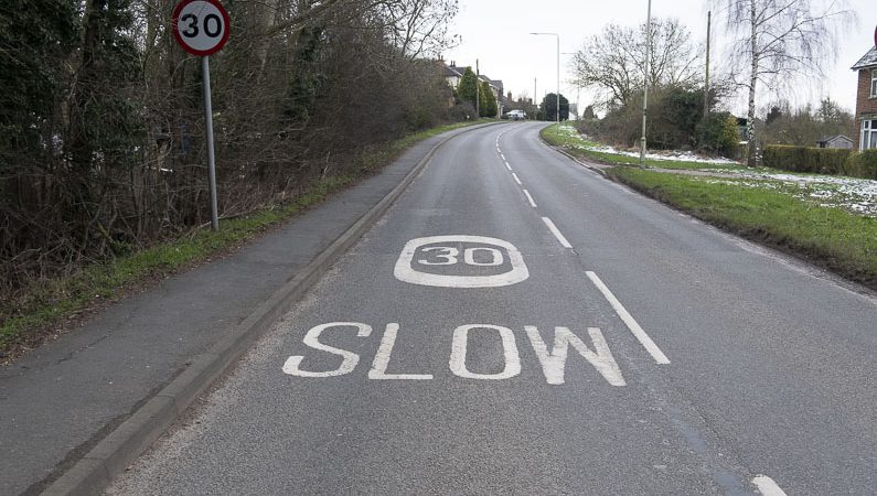 30 mph speed limit and the word slow, painted on the road