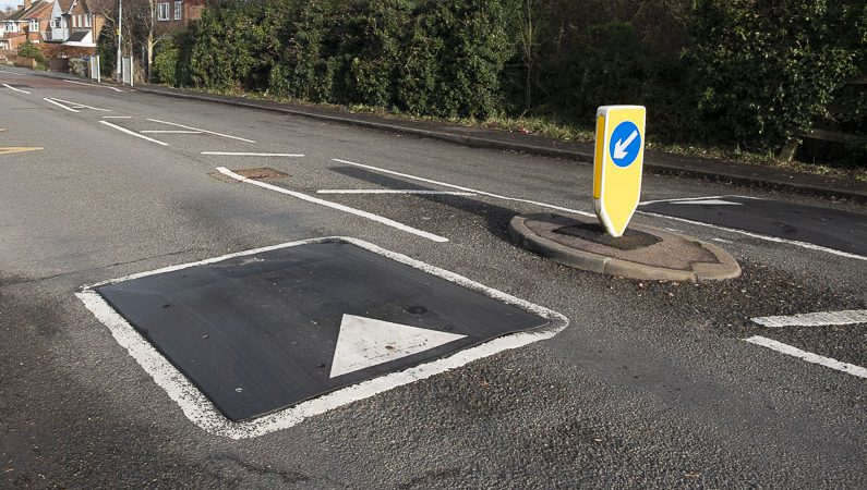 A short raised rounded device in the centre of a road lane