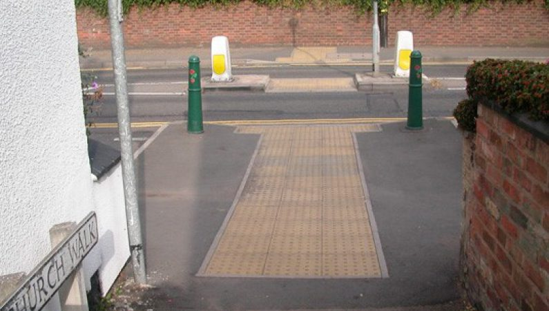 Raised surface paving near a junction to help sighted and visually impaired pedestrians