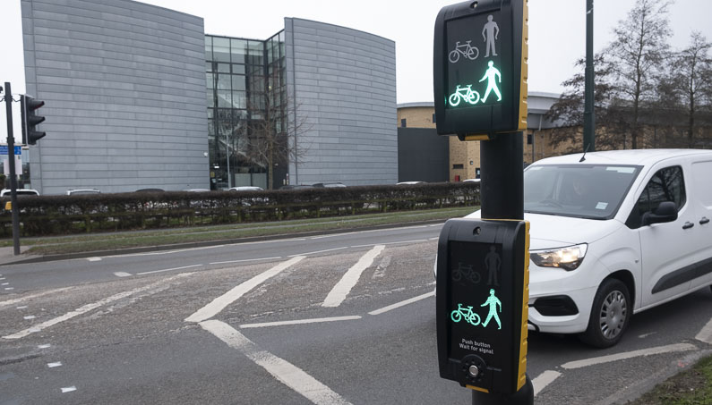 Toucan crossing showing a green (go) bike and pedestrian light and white van waiting