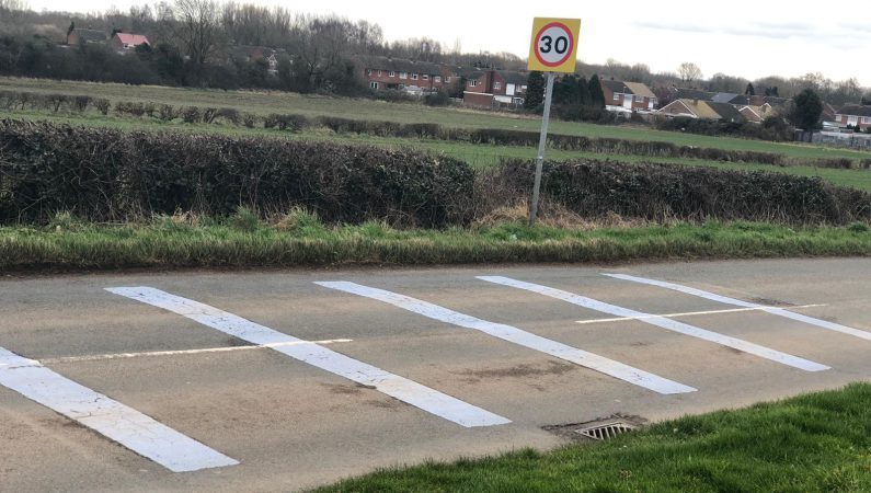 Known as rumble strips, they're a series of slightly raised strips which cover the width of the road